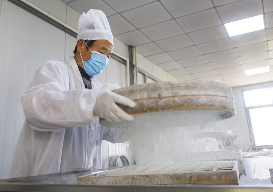 คนงานเจียงซูเร่งมือทำ 'ขนมเข่ง' ก่อนถึงเทศกาลตรุษจีน