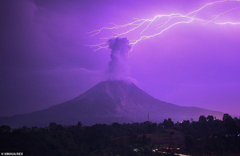 """ช่างภาพลั่นชัตเตอร์ ท้องฟ้าสีม่วง-สายฟ้าฟาด เหนือภูเขาไฟ """"ซีนาบุง"""" พ่นเถ้าถ่าน"""